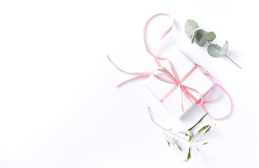 White gift box with pink ribbon and dry eucalyptus leaves on white background. Flat lay. Copy space