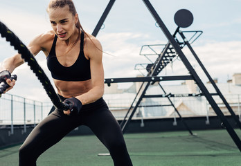 Woman using battle ropes during strength training on rooftop. Young female working out outdoors.