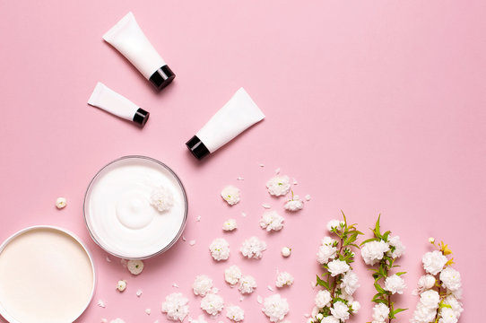 Beauty Spa concept. Opened plastic container with cream, cosmetic bottle containers, spring White flowers on pink background Flat lay top view. Herbal dermatology cosmetic hygienic cream organic