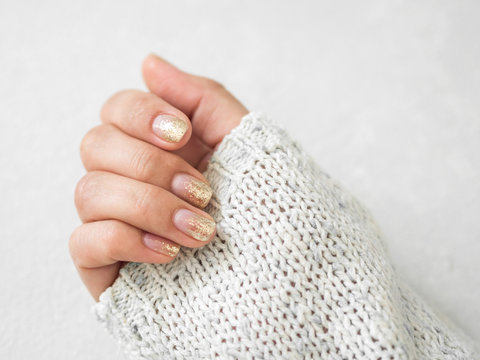 Manicure salon concept. Beautiful women hands with golden nail manicure on a white background. Gold nail polish. Closeup
