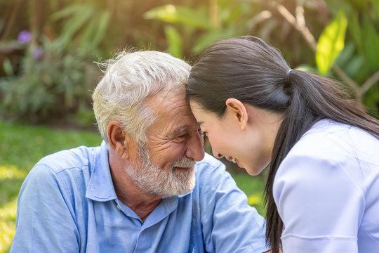 Smiling nurse and eldery senior man touching heads in garden in nursing home