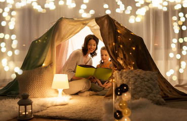 family, hygge and people concept - happy mother and little daughter reading book in kids tent at...