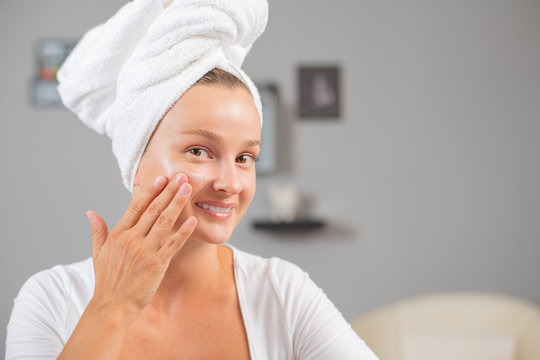 Happy young woman applying cream to her face. Woman face skin care.