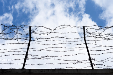 Barbed wire fence..Silhouette of barbed wire fence on top of concrete wall against cloud blue sky ,low angle view..