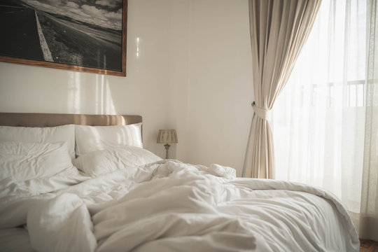 White interior of cozy bedroom with  morning light. Cozy bedroom beside window and sunlight in the morning horizontal background.