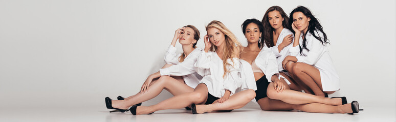 panoramic shot of five sexy multiethnic feminists wearing white shirts and heels and sitting on grey