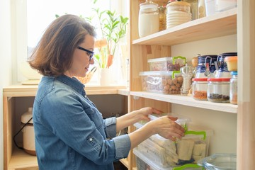 Woman at home in kitchen, near wooden shelves with food
