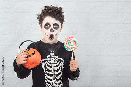 Happy Halloween.funny child in a skeleton costume eating lollipop in halloween