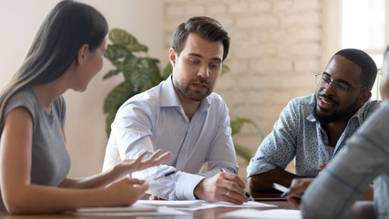 Successful male corporate leader explain paperwork at group office briefing