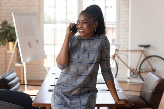 Smiling black businesswoman talking on phone making call in office