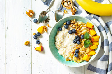 Healthy food for Breakfast, vegetarian, vegan, alkiline diet food concept. Oatmeal porridge with chia, banana and blueberry on fruits and nuts on a white wooden table. Top view flat lay.