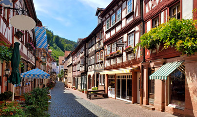 Fototapete - Beautiful restaurant lined street of traditional half timbered buildings in the town of Miltenberg, Bavaria, Germany