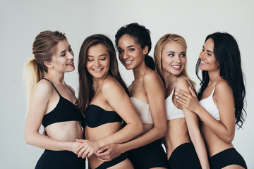 five sexy multiethnic young women in underwear embracing and smiling isolated on grey