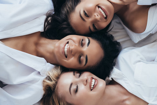 top view of three smiling multiethnic women in white shirts lying with closed eyes