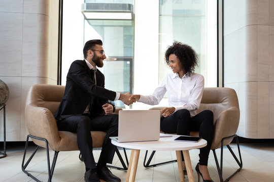 Smiling diverse business partners shaking hands at meeting