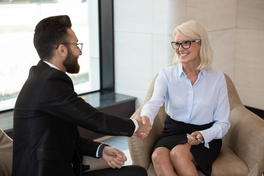 Smiling mature businesswoman shaking hand of business partner at meeting