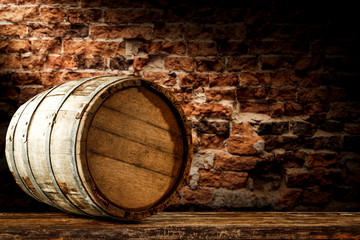 A barrel on wooden table and brick wall background.