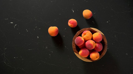 Flat lay photo - apricots in small wooden bowl, on black marble like table, space for text left side