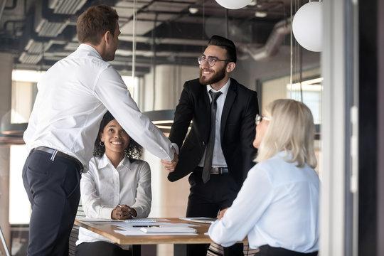 Smiling businessmen partners shaking hand, making agreement at meeting