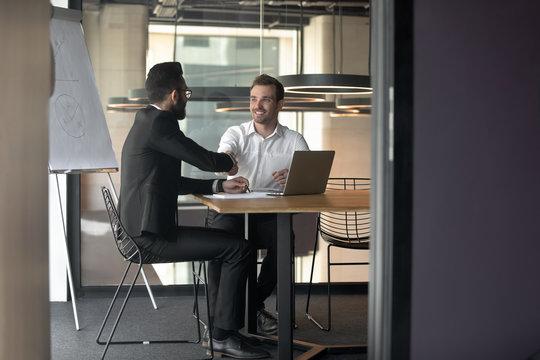 Businessmen partners handshaking at meeting in boardroom