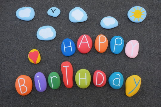 Creative Happy Birthday text with colored and carved sea stones over black volcanic sand