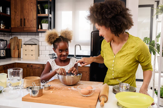 Mother Teaching Child to Cook and Help in the Kitchen. African American Mother and Daughter making cookies at home.
