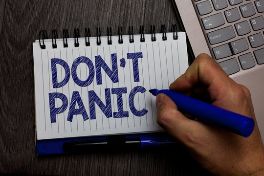 Writing note showing Don t not Panic. Business photo showcasing sudden strong feeling of fear prevents reasonable thought Man holding marker spiral notebook computer keyboard wooden background