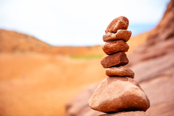Zen stones stack, blur red desert background Arizona, US.
