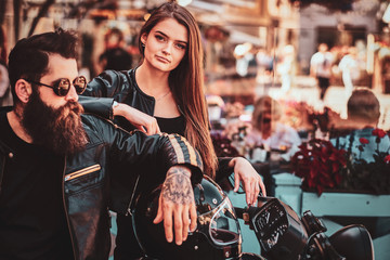Beautiful couple with brutal biker and his sexy gilfriend are chilling near cefeteria with motorbike.