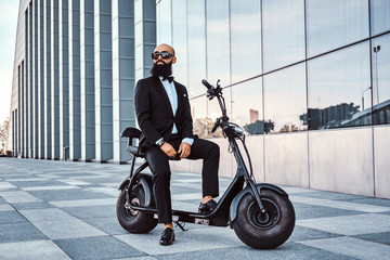 Elegant bald businessman in sunglasses is sitting on his electrical scooter near glass building.