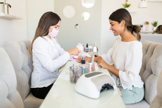 Side View Of Women Sitting At Nail Salon