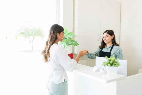 Satisfied Client Paying At Reception Desk In Spa