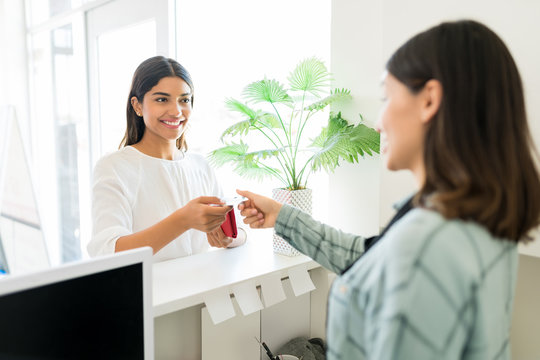 Client Paying For Beauty Treatment To Receptionist In Spa