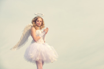 Valentines day pray cupid. Pray. Enjoying magic moment. Girl dressed as an angel on a light heaven background. Real fairy from magical stories. Teenager Cherub Cupid.