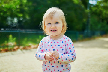 smiling one year old girl walking in park