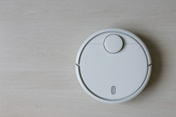 A robot vacuum cleaner removes debris on a laminate. Smart cleaning. White robotic vacuum cleaner.