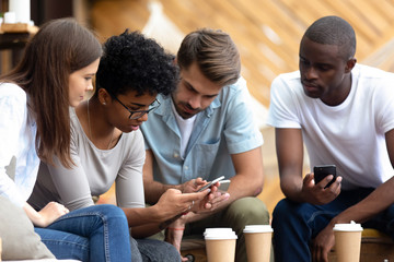 Diverse young people busy using smartphones together