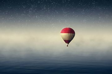 Poster Ballon Hot air balloon over the sea at night