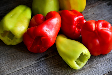 Green and red bell peppers on a rustic table.