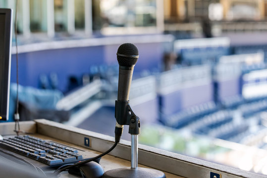 Microphone resting in holder on desk of announcers booth for baseball stadium.