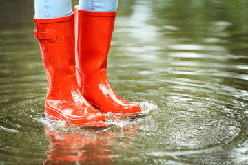 Woman with red rubber boots in puddle, closeup. Rainy weather