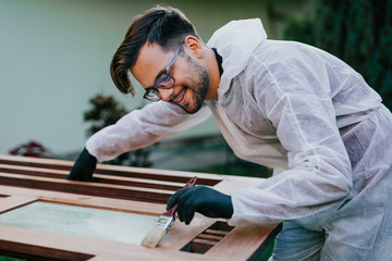 Young nice looking handyman with eye glasses and protective workwear painting outside window with...