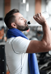 Young adult man drinking bottle of water on trreadmill in gym.