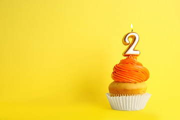 Birthday cupcake with number two candle on yellow background, space for text