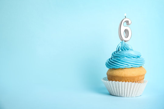 Birthday cupcake with number six candle on blue background, space for text