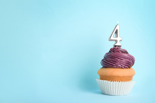 Birthday cupcake with number four candle on blue background, space for text
