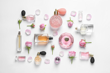 Fototapeta Different perfume bottles and flowers on white background, top view