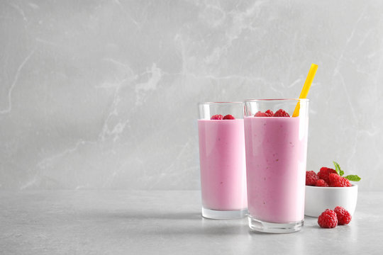 Glasses of tasty smoothie with raspberries on light table. Space for text