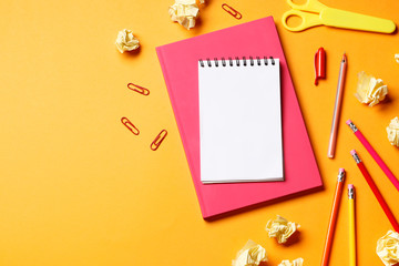 Notebook with pen on an orange background and school supplies. Place for text. Top view.