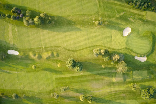 Aerial view of links golf course during summer showing green and bunkers at driving range